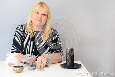 Portrait of beautiful middle age woman sits near a fortune teller desk with a tarot cards and candles.