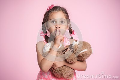 Portrait of Child Girl Hugging Her Soft Toy Bear on Pink Background and Doing Gesture to Silence