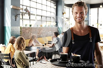 Portrait Of Waiter Serving Customers In Busy Coffee Shop