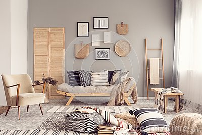 Stylish living room interior design with scandinavian settee, grey wall and natural accents