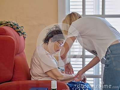 Old senior in her wing chair and the geriatric nurse helps her  to cover a wound with plaster
