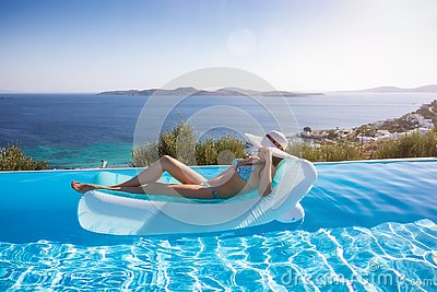 Woman enjoys the view to the Aegean Sea floating on a swimming pool, Mykonos, Greece