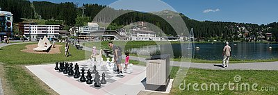 Tourists enjoy summer activities on the lakeshore in Arosa with the train and cable railway station in the background