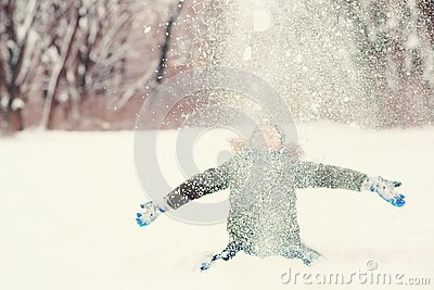 Happy kid having fun playing in the snow. Cute boy is throwing snow, enjoing snowy weather. Happy winter and christmas holidays.