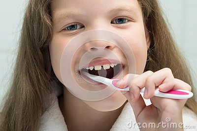 Little girl in a white robe smiling brushes her teeth, close-up