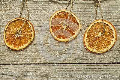 Vintage wooden background with Christmas wreath - dried orange slices hang on rope and falling snow. Greeting card with copy space