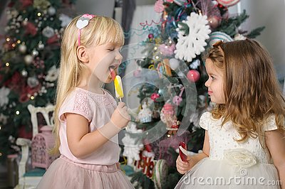 Two cute little girls in a festive New Year`s atmosphere with colored lollipops