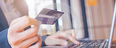 Woman hand holds a blue credit card.And are using a laptop computer.Web banner