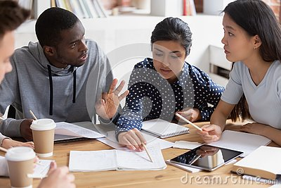 Focused diverse students discuss ideas studying in class together