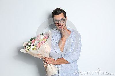 Young handsome man with beautiful flower bouquet on light