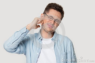Studio headshot young man suffers from earache or noise