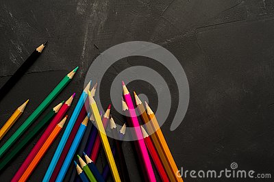Colored sharpened pencils lie on the dark surface