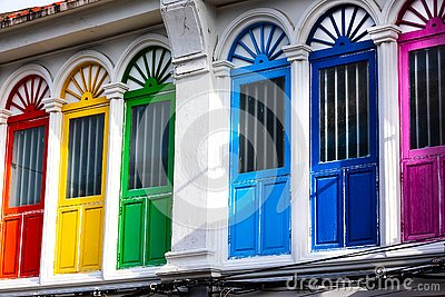 Six colorful doors or windows outside on the facade of an ancient house