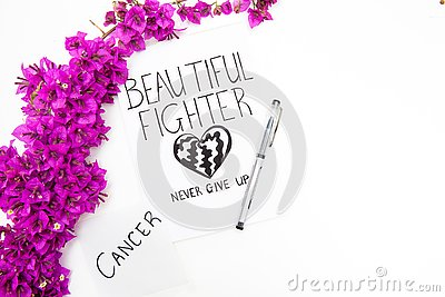 Cancer word written on note with pen and wild purple flowers. Beautiful fighter inspirational card.