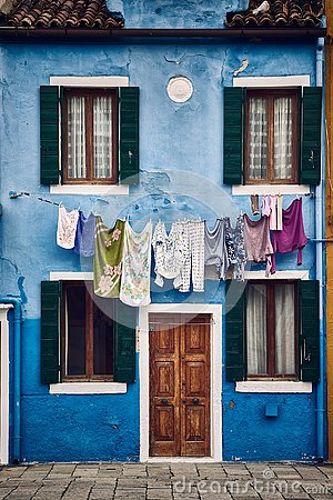 Beautiful vertical symmetric shot of a suburban blue building with clothes hanging on a rope