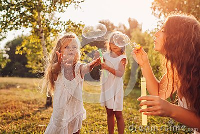 Mother helps daughters to blow bubbles in summer park. Kids having fun playing and catching bubbles outdoors