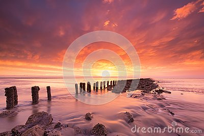 Beautiful red sunset at the sea with rock and a dramatic sky in the foreground - Travel image