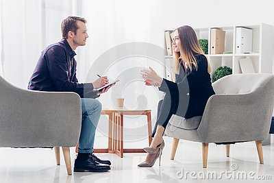 Side view of cheerful businesswoman in suit sitting on armchair and giving interview to journalist