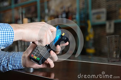 Man using credit card  for non cash payment in cafe, closeup. Space for text