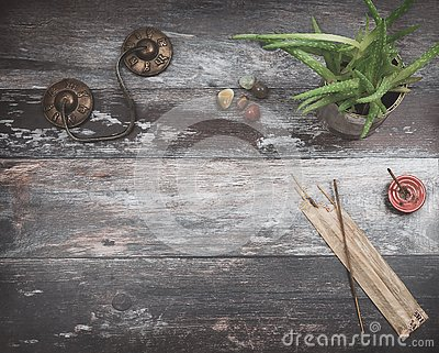 Rustic wooden table with green plant, burning incense, small energy healing stones and Tibetan meditation prayer bells