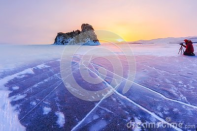 Photographer takes pictures winter ogoy island at sunrise in the ice of Lake Baikal, Russia