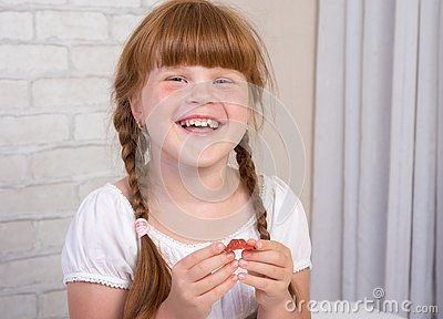 Little red-haired girl in a white dress holds a plate in her hands to correct a bite of teeth