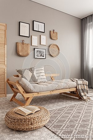 Gallery of posters in black frames and wicker kinck knack on beige wall of trendy living room interior with long settee with