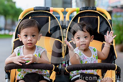 Two brothers sit in a stroller. Adorable twin baby boys sitting in stroller and smiling happily. Childhood emotions.