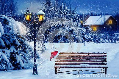 Christmas art card. Santa hat on a bench in the snow against the background of the Christmas winter forest. Village house in the b