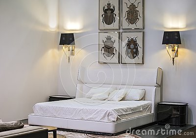 Modern interior, white bedroom with a double bed, paintings and lamps on the walls. Beautiful design of the bedroom