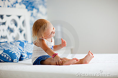 Portrait of playful toddler girl sitting on bed
