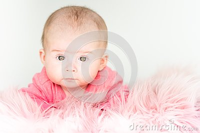 Cute baby girl lying on furry blanket on the bed at home and watching curiously