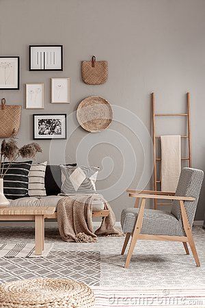 Stylish vintage armchair in contemporary living room interior with futon settee and wooden scandinavian ladder with blanket