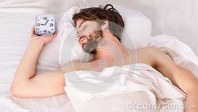 Lazy man happy waking up in the bed rising hands in the morning with fresh feeling relaxed. Man eyes are closed with