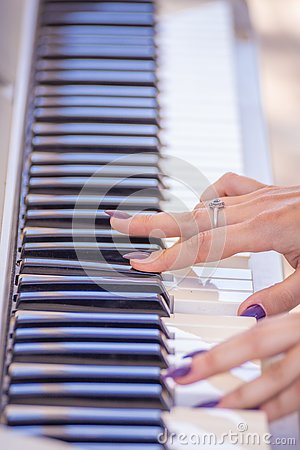 Female fingers on the keys of a musical instrument synthesizer