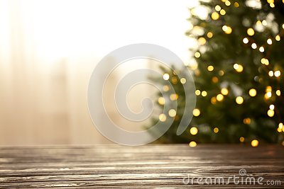 Empty table and blurred fir tree with yellow Christmas lights on background, bokeh effect