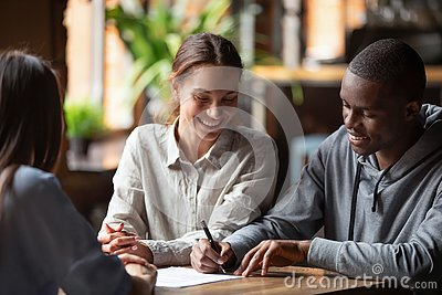 Happy mixed ethnicity couple customers sign mortgage loan contract