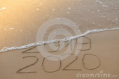 Inscription 2019 and 2020 on beach sand, wave covering 2019 digits. New Year 2020 coming concept