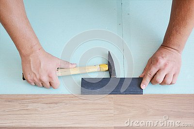 Contractors installing wooden laminate flooring with insulation and soundproofing sheets. Man laying laminate flooring. Man laying