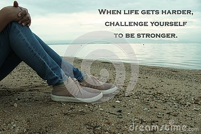 Inspirational Quote-When life gets harder, challenge yourself to be stronger. With a thoughtful young woman sitting in the beach