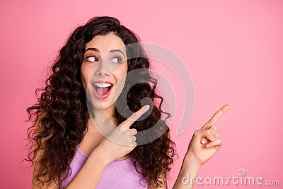 Photo of cheerful funky funny crazy nice glad sweet attractive girl pointing at emptiness away from her surprisingly