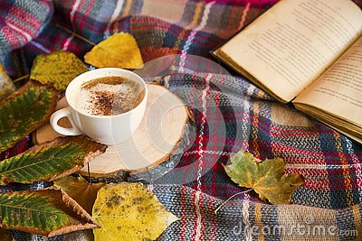 Autumn coffee cup with cozy blanket, fall deco warm home weekend with coffee cup, a book and dried leaves