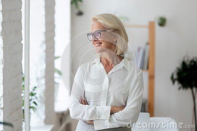 Smiling aged businesswoman look in distance thinking