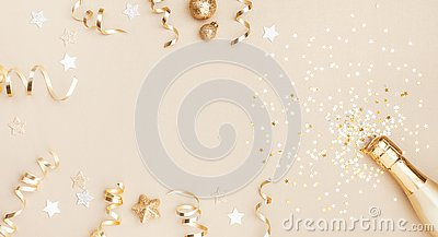 Champagne bottle with confetti stars, holiday decoration and party streamers on gold festive background. Christmas flat lay