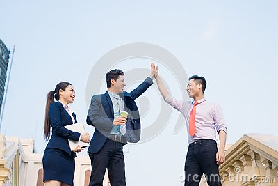 Happy businessmen and businesswoman celebrate success in project task achievement