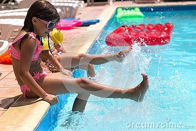 Two little girls sitting on the poolside, playing, splashing water; summertime background