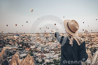 Young attractive girl in a hat stands on the mountain with flying air balloons on the background. Finger pointing girl