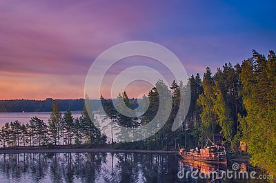 Small fishing or pleasure boat boat moored on Paijanne lake. Beautiful sunrise scape with stone beach, pine forest and water. Lake
