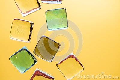 Stylish yellow background with transparent ice-like cubes for drinks. Flat lay macro photo
