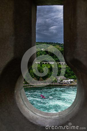Dramatic Keyhole view of Rhein Rhine water fall in switzerland, background has green forest and dramatic cloudy sky